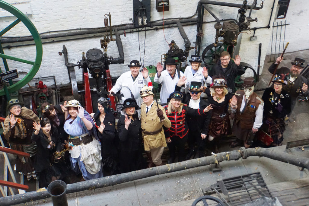 Steampunk visitors dressed in steampunk Victorian style clothing inside Crofton Steam engine house